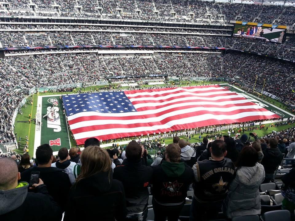 large american flag on football field