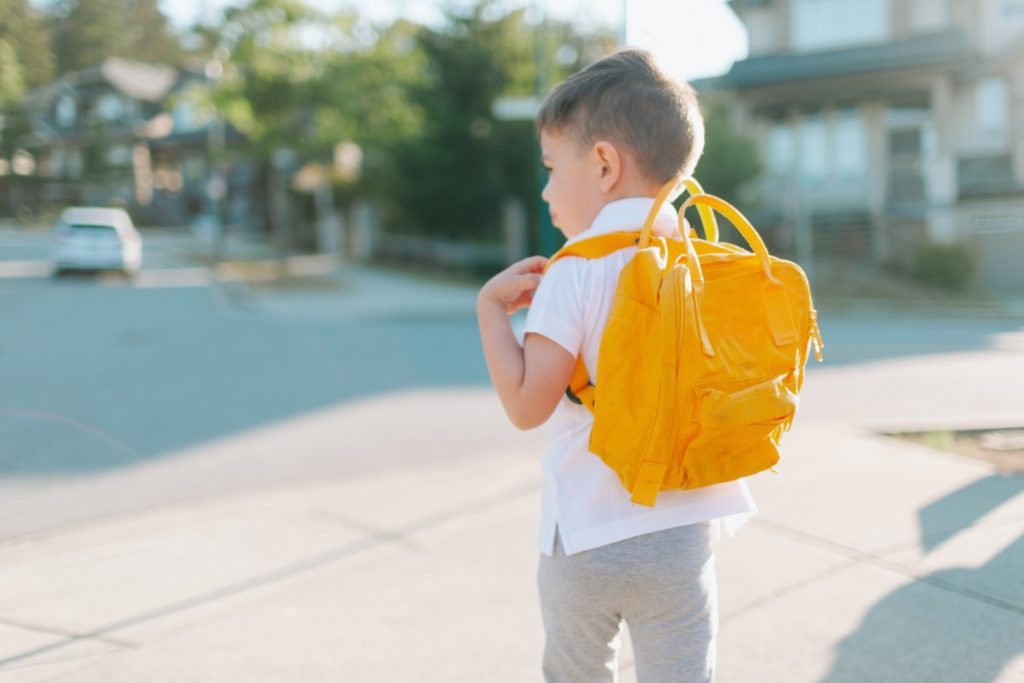 A little boy walking to school with a yellow backpack.