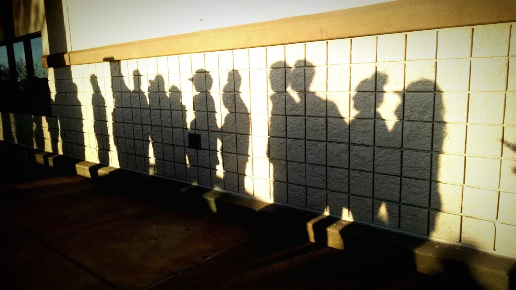 people standing in line with shadow on wall