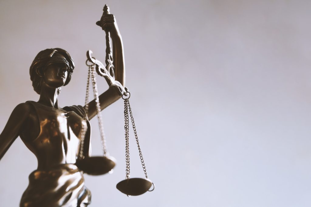 Lady Justice or Justitia statue with blindfold and scales - law and legal concept